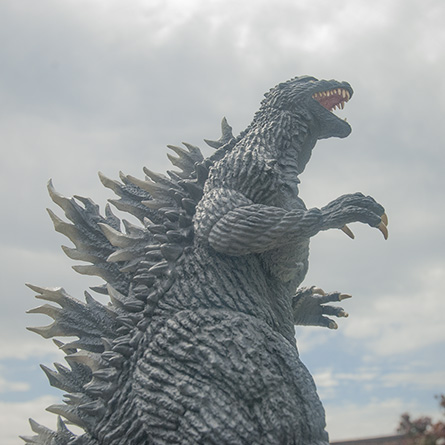 X-Plus 30cm Godzilla 2003 vinyl figure against sky. Photo copyright, John Stanowski.