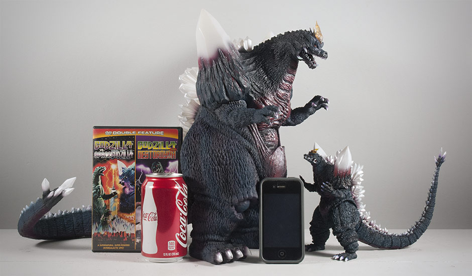 X-Plus Space Godzilla beside S.H. Monsterarts figure, DVD, iphone and soda can.