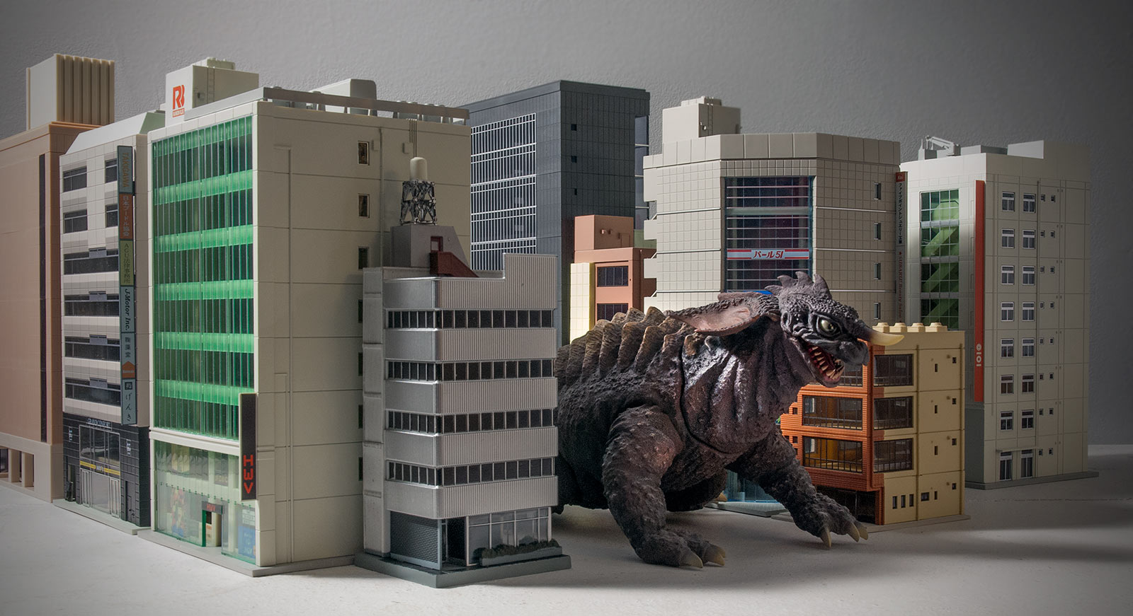 Wide shot of the X-Plus Crawling Baragon vinyl with N-Scale buildings.