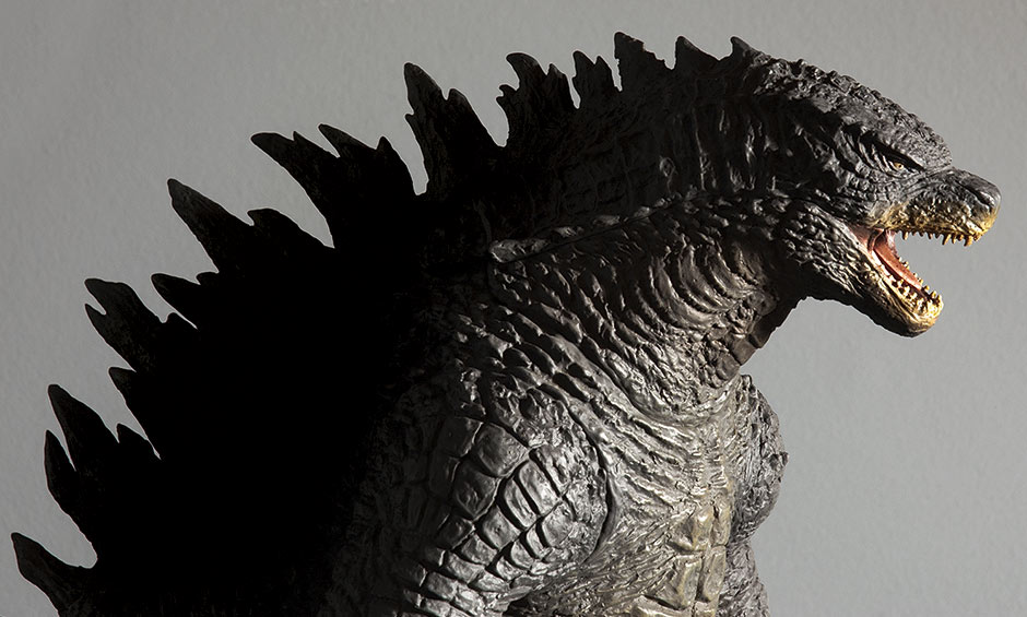 Stylized photo of the X-Plus Godzilla 2014 vinyl figure with dark fins.