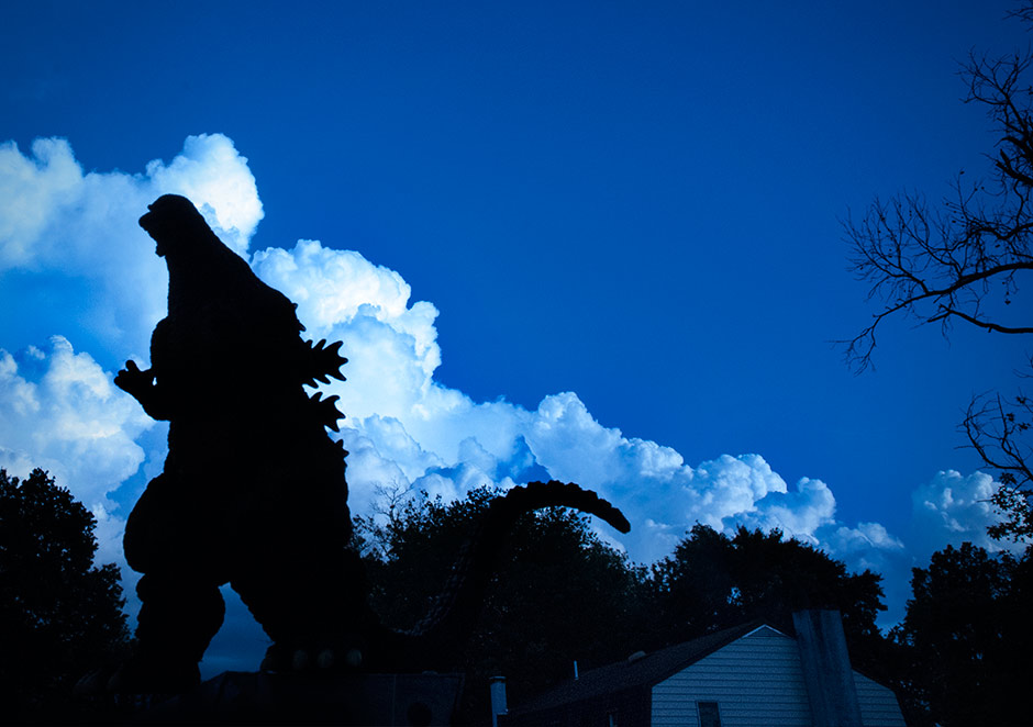 Stylized shot of Godzilla 1995 walking through neighborhood.