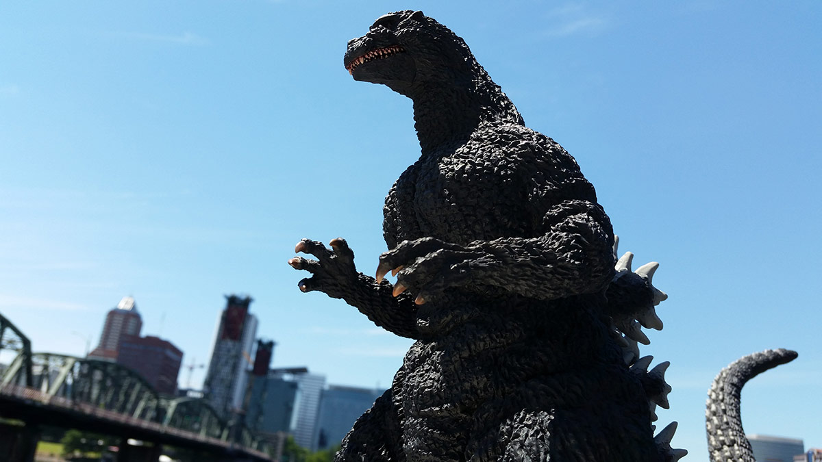 X-Plus Yuji Sakai Godzilla 1991 vinyl figure against the downtown Portland skyline.